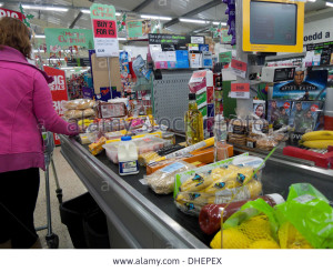 a-woman-at-a-checkout-counter-filled-with-groceries-food-in-co-op-DHEPEX